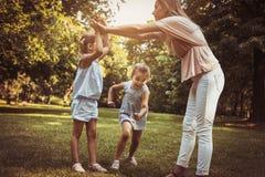 Madre con el niño dos en prado Madre que celebra las manos con la muchacha Imagen de archivo