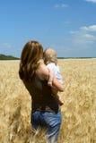 Madre con el niño en el campo de trigo Fotos de archivo libres de regalías