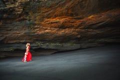 Madre con el niño en gruta de la playa del mar imagenes de archivo