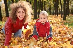 Madre con el niño en las hojas Imagen de archivo