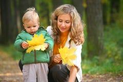 Madre con el niño en madera otoñal Fotografía de archivo libre de regalías