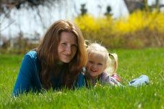 Madre con el niño en una hierba Imagenes de archivo