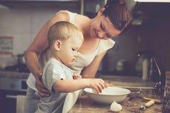 Madre con el niño que cocina junto Imágenes de archivo libres de regalías