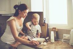 Madre con el niño que cocina junto Imagenes de archivo