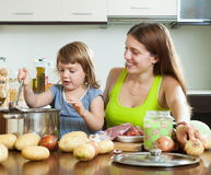 Madre con el niño que cocina la sopa Fotografía de archivo
