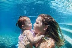 Madre con el niño que nada bajo el agua en piscina azul de la playa Fotografía de archivo