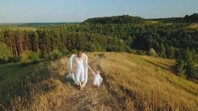 Madre con el niño vestido como los ángeles caminan en naturaleza almacen de metraje de vídeo
