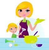 Madre con el niño que cocina el alimento sano en cocina Fotos de archivo libres de regalías