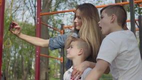 Madre con el pelo largo rubio que hace una foto con sus dos hijos jovenes en el patio almacen de metraje de vídeo