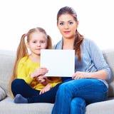 Madre con el tablero en blanco blanco de la demostración de la hija Imagenes de archivo