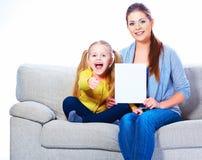 Madre con el tablero en blanco blanco de la demostración de la hija Imágenes de archivo libres de regalías