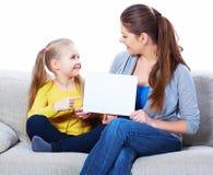 Madre con el tablero en blanco blanco de la demostración de la hija Fotografía de archivo