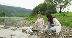 Madre con el tiro de la hija las piedras en el río momentos felices de maternidad Para dar cinco Fondo de las montañas metrajes