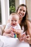 Madre con el viejo bebé de seis meses que juega en regazo Foto de archivo