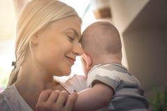 Madre con gli occhi chiusi che gode con il suo neonato immagine stock