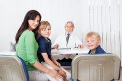Madre con i bambini all'ufficio dei medici Immagine Stock