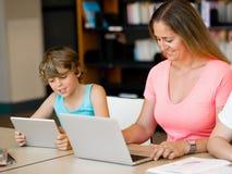 Madre con i bambini in biblioteca Fotografia Stock