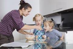 Madre con i bambini che cuociono e che assaggiano la pastella del biscotto in cucina Immagini Stock