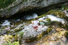 Madre con i bambini che si siedono da un'insenatura della montagna di estate, raffreddante fotografie stock libere da diritti