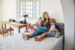 Madre con i bambini che si siedono insieme sul libro di lettura del letto Fotografie Stock Libere da Diritti