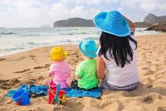 Madre con i gemelli sulle feste della spiaggia Immagine Stock Libera da Diritti