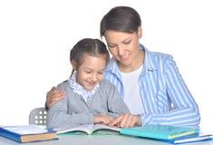Madre con i libri di lettura della figlia Fotografia Stock Libera da Diritti