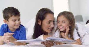 Madre con i suoi bambini che leggono il libro di storia in camera da letto a casa 4k video d archivio