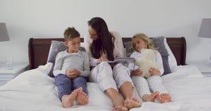 Madre con i suoi bambini che leggono il libro di storia in camera da letto a casa 4k archivi video