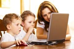 Madre con i suoi bambini che per mezzo del computer portatile fotografia stock libera da diritti
