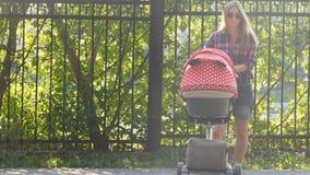 Madre con il bambino in carrozzino che cammina nel parco archivi video
