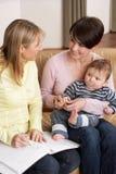 Madre con il bambino che comunica con l'ospite di salute Immagini Stock Libere da Diritti