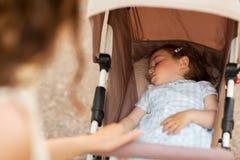 Madre con il bambino che dorme in passeggiatore Fotografie Stock