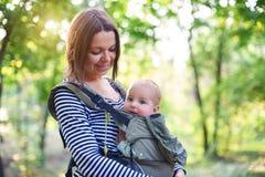 Madre con il bambino di trasporto ergobaby nella foresta fotografie stock