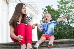 Madre con il bambino gridante emozionale sulle scale di vecchia costruzione nel parco Immagini Stock Libere da Diritti
