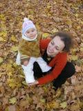 Madre con il bambino sul campo di autunno Immagini Stock Libere da Diritti