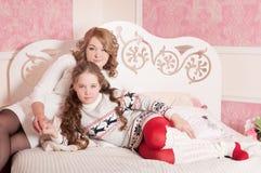 Madre con il bambino sul sofà, fondo rosa Fotografie Stock Libere da Diritti