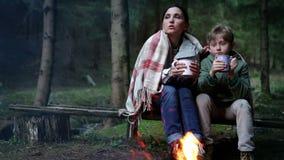 Madre con il figlio che beve il tè e che parla vicino al fuoco di accampamento vicino della foresta video d archivio