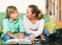 Madre con il figlio che fa compito Immagini Stock