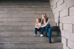 Madre con il figlio che si siede sull'le scale Immagini Stock
