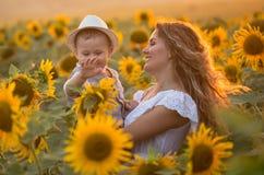 Madre con il figlio del bambino nel giacimento del girasole Fotografia Stock