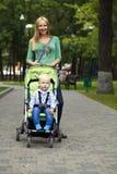 Madre con il figlio di due anni nel parco di estate Fotografia Stock