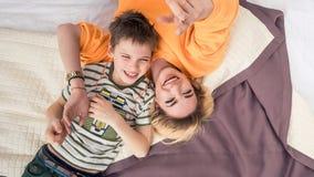 Madre con il figlio sul divertiresi del letto, della madre e del figlio fotografie stock
