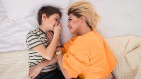 Madre con il figlio sul divertiresi del letto, della madre e del figlio fotografia stock libera da diritti