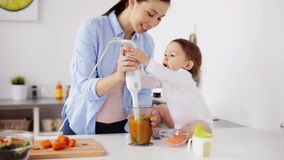 Madre con il miscelatore che cucina alimenti per bambini a casa stock footage