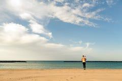 Madre con il neonato che gode dell'alba su una spiaggia Fotografia Stock