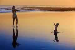 Madre con il piccolo bambino sulla spiaggia del mare di tramonto fotografia stock libera da diritti