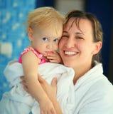 Madre con il suo bambino in accappatoio Fotografia Stock