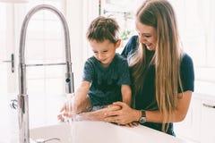 Madre con il suo bambino che gioca nel lavandino di cucina Fotografia Stock