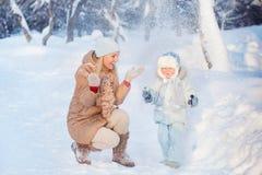 Madre con il suo bambino che gioca nell'inverno Immagine Stock