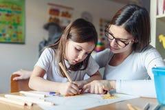 Madre con il suo bambino che ha disegno di divertimento e creativo di tempo fotografia stock libera da diritti